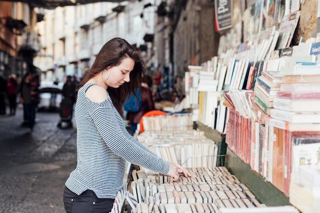 Menina procura livros na livraria Foto gratuita