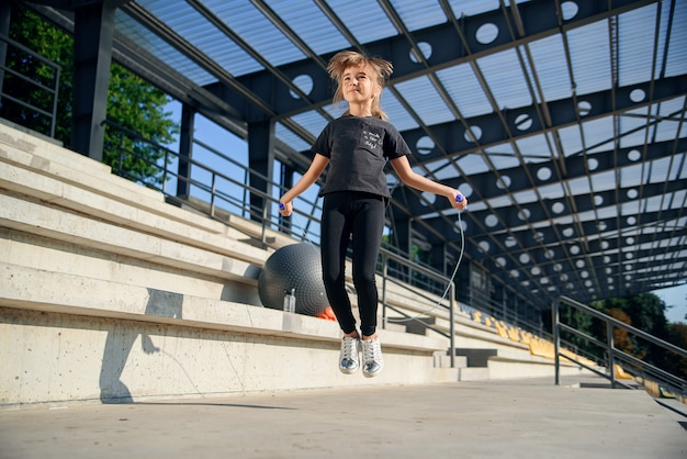 Menina pulando com pular corda no estádio. fêmea de aptidão ativo fazendo exercícios ao ar livre. estilo de vida saudável e esportivo desde a infância. Foto Premium