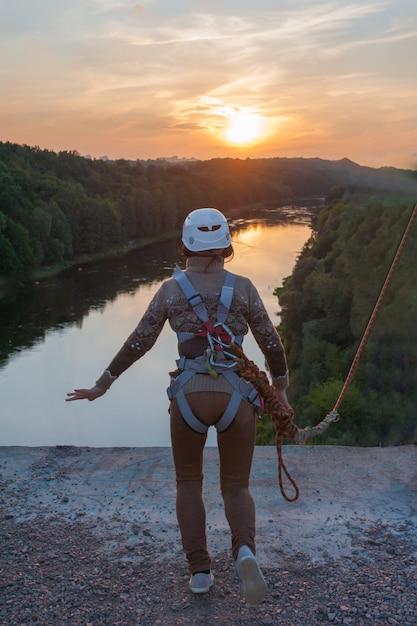 Menina pulando da ponte. uma garota com um tempo incrível está envolvida no estilo livre no bungee jumping. uma jovem executa um truque reverso no bungee jumping. ir ao pôr do sol extreme young. Foto Premium