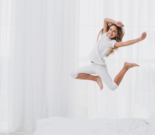 Menina pulando enquanto olha para a câmera Foto gratuita