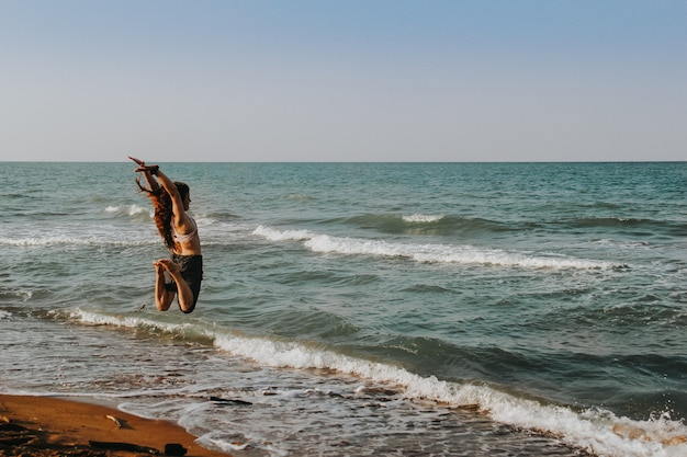 Menina pulando no ar na praia. conceito de verão. Foto Premium