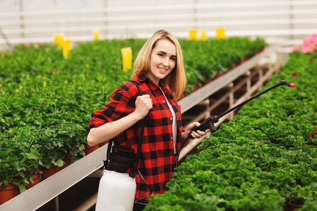 Menina pulveriza as plantas. garota trabalhando em estufas. plantas fertilizantes Foto Premium