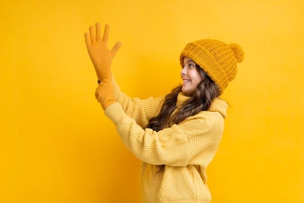 Menina puxando a luva na mão dela Foto gratuita