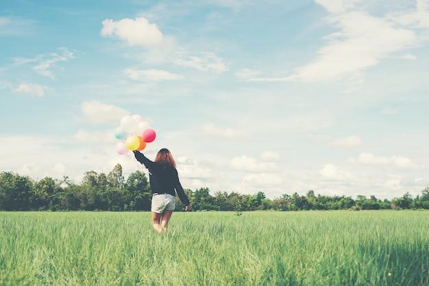 Menina que anda com balões coloridos Foto gratuita