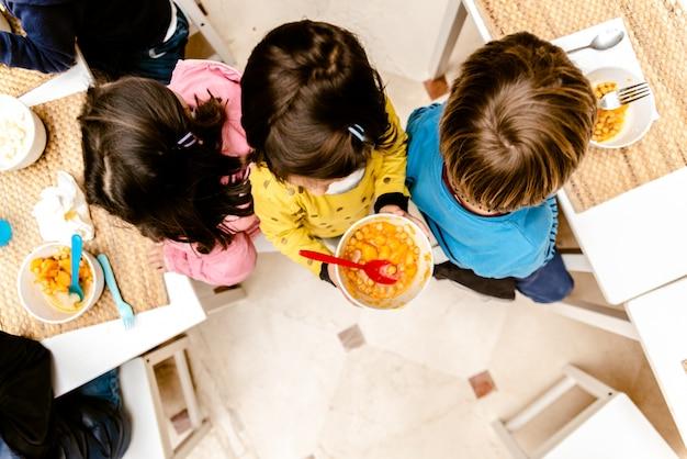 Menina que anda com uma bacia de guisado na sala de jantar de seu infantário, vista superior, com espaço da cópia. Foto Premium