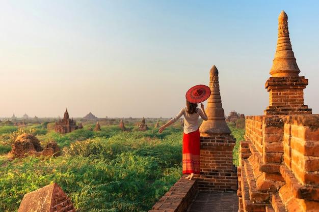 Menina que está com guardar o guarda-chuva, bagan, myanmar. Foto Premium