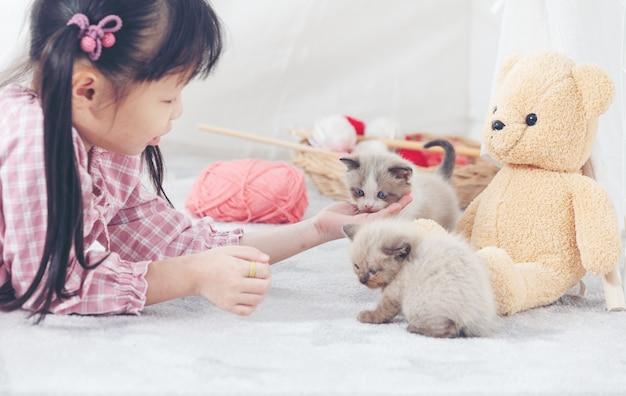 Menina que joga com gato em casa, conceito do navio do amigo. Foto Premium