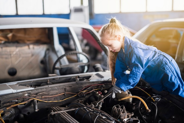 Menina que repara o carro com chave inglesa Foto gratuita