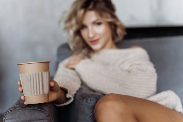 Menina que senta-se em um sofá que prende um vidro do café em um braço outstretched. concentre-se em um copo de café Foto Premium
