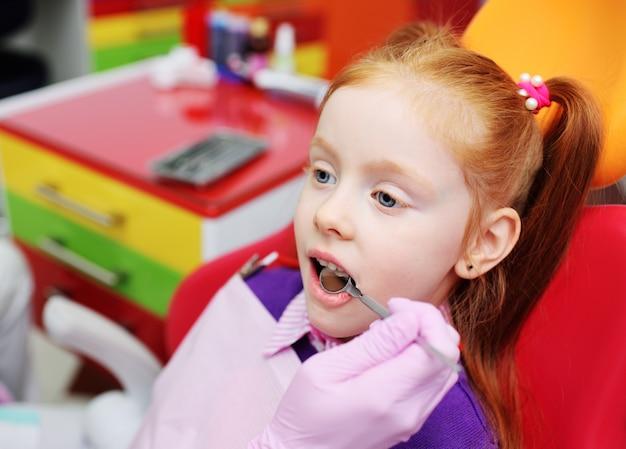 Menina que sorri na cadeira dental vermelha. o dentista examina os dentes do paciente da criança. Foto Premium