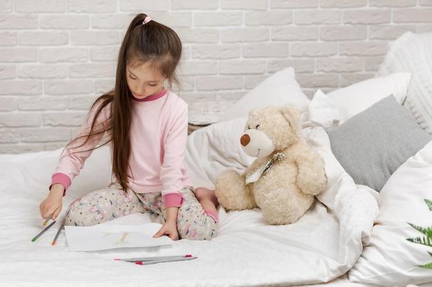 Menina que tira retratos ao encontrar-se na cama. Foto Premium