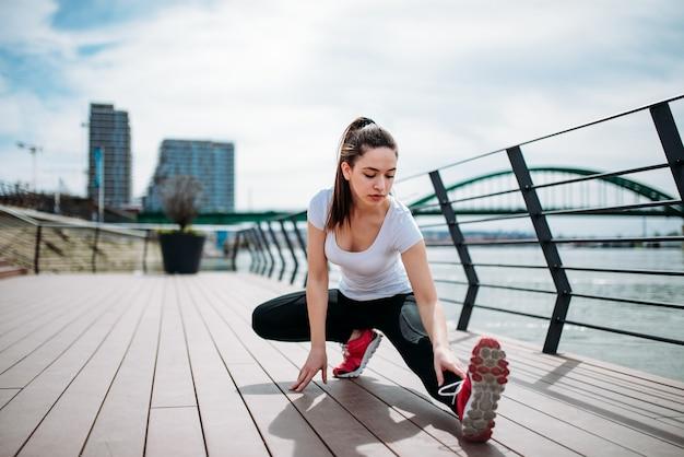Menina que treina no cais que estica os pés e que faz exercícios. Foto Premium