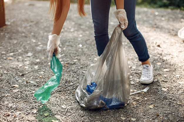 Menina recolhe lixo em sacos de lixo no parque Foto gratuita