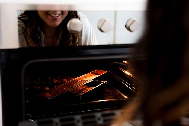 Menina refletida no forno Foto gratuita
