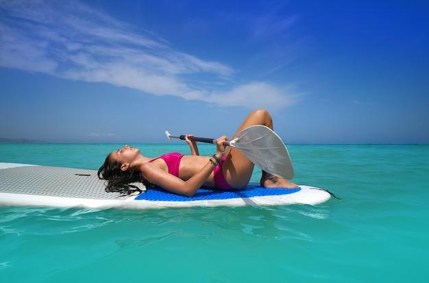 Menina relaxada deitada na prancha de surf paddle Foto Premium