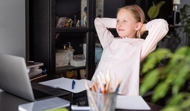 Menina relaxante enquanto faz uma aula on-line Foto gratuita