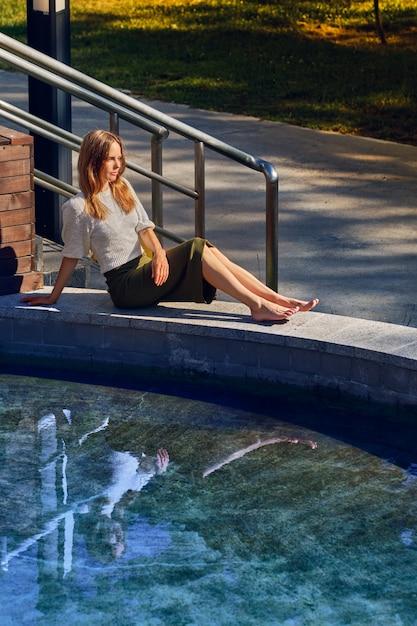 Menina relaxante sob o sol perto da água no dia quente sensual Foto Premium
