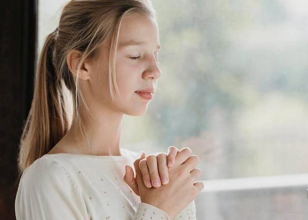 Menina rezando com espaço de cópia Foto gratuita