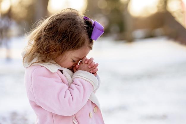 Menina rezando em um jardim coberto de neve sob a luz do sol a uma distância borrada Foto gratuita