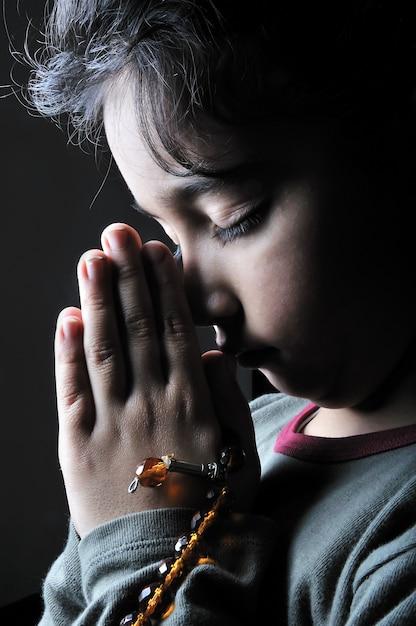 Menina rezando no escuro Foto Premium
