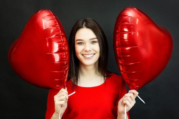 Menina ri lindamente segurando balões. uma bela morena sorridente está segurando dois balões em forma de coração perto do rosto. Foto Premium