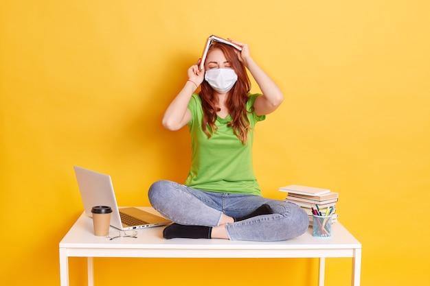 Menina ruiva com máscara médica se senta com as pernas cruzadas na mesa branca com o livro acima da cabeça, mantém os olhos fechados, vestindo jeans e camiseta verde, rodeada de lap top, café, canetas. Foto gratuita