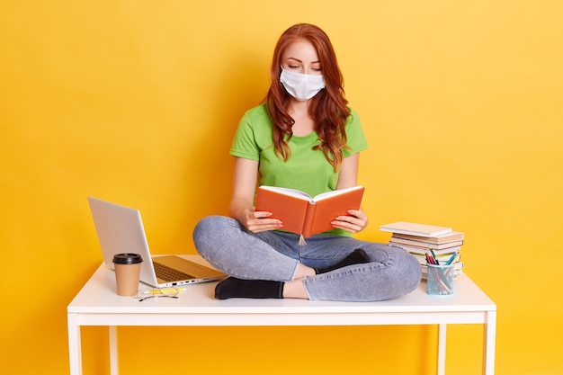 Menina ruiva com máscara médica sentada na mesa com computador e livros, lendo, parece concentrada Foto gratuita