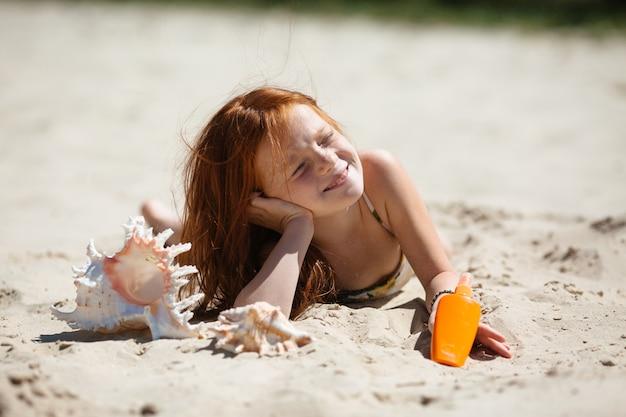 Menina ruiva deitada na areia tomando banho de sol Foto Premium