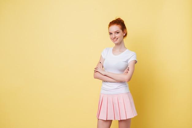 Menina ruiva sorridente em t-shirt e saia posando com os braços cruzados e olhando Foto gratuita