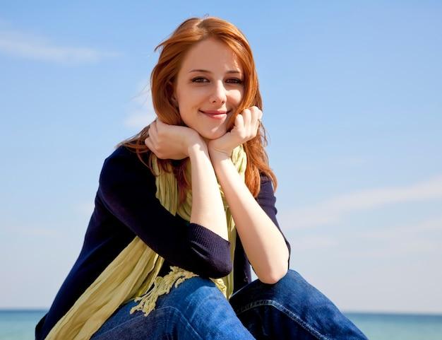 Menina ruivo bonita nova na praia no tempo de mola. Foto Premium