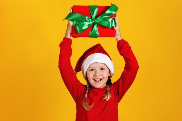 Menina segura uma caixa com um presente de natal na cabeça. Foto Premium