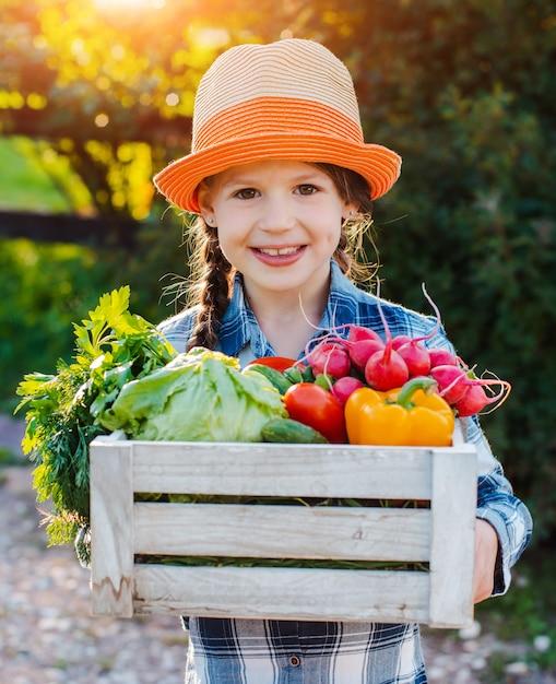 Menina, segurando a caixa de legumes orgânicos frescos Foto Premium