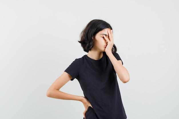 Menina segurando a mão no rosto em t-shirt preta e olhando com sono, vista frontal. Foto gratuita