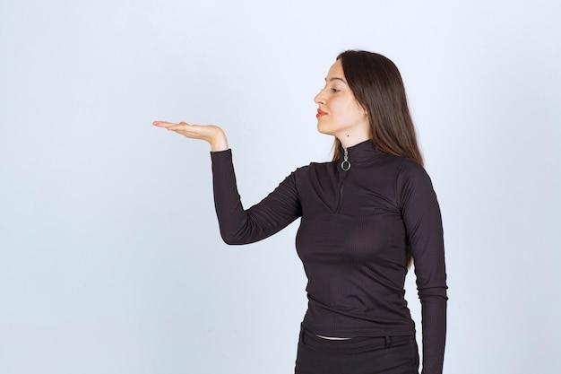 Menina segurando algo na mão e apresentando-o. Foto gratuita