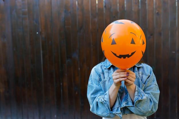 Menina segurando ballon com cara de abóbora Foto Premium