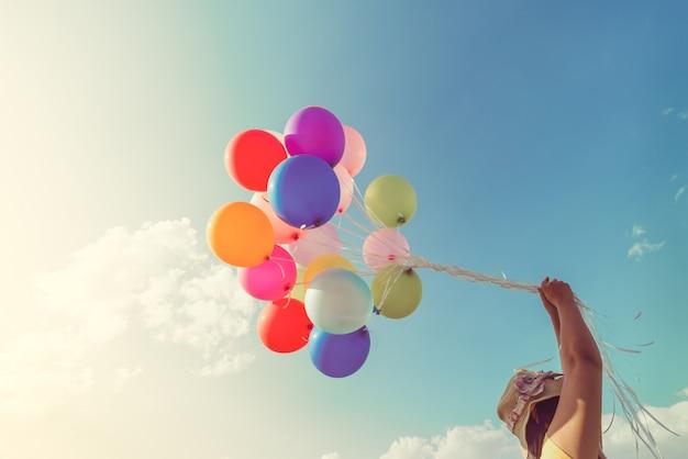 Menina segurando balões multicoloridos Foto Premium