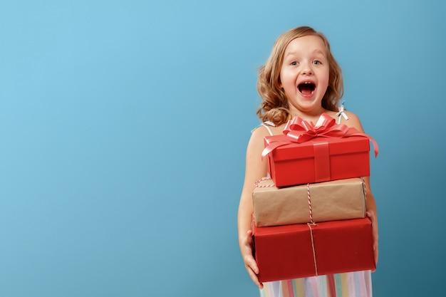 Menina segurando caixas com presentes. Foto Premium