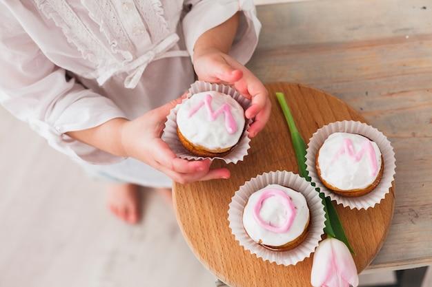 Menina, segurando, cupcake, com, mãe, inscrição Foto gratuita