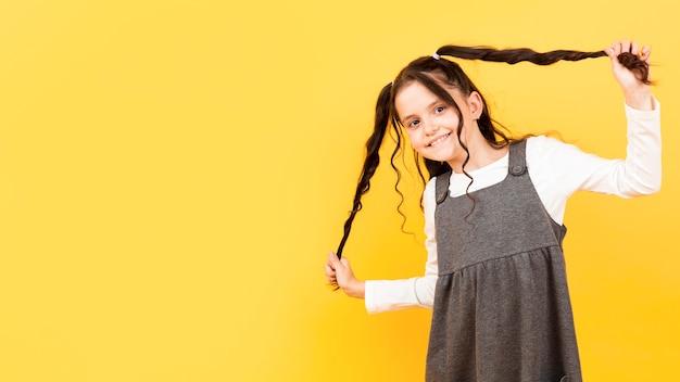 Menina, segurando, dela, pigtails, cópia-espaço Foto gratuita