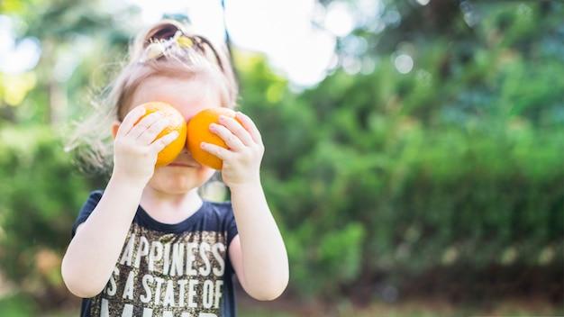 Menina, segurando, dois, laranjas, sobre, dela, olhos Foto gratuita