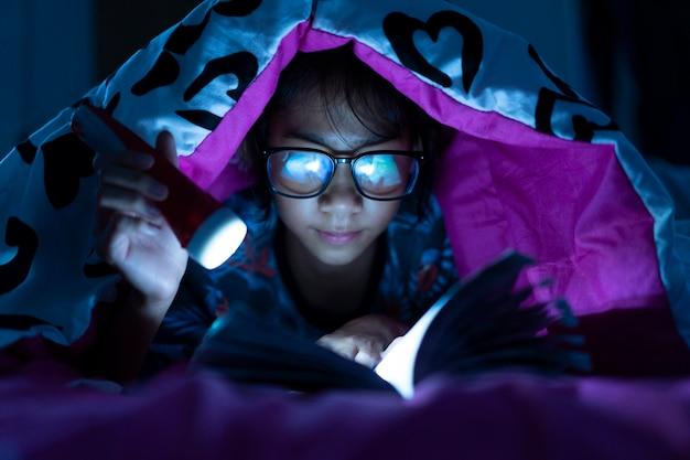 Menina, segurando, lanterna, enquanto, desgaste, óculos, leitura, livros, cobertor, em, cama, sala Foto Premium