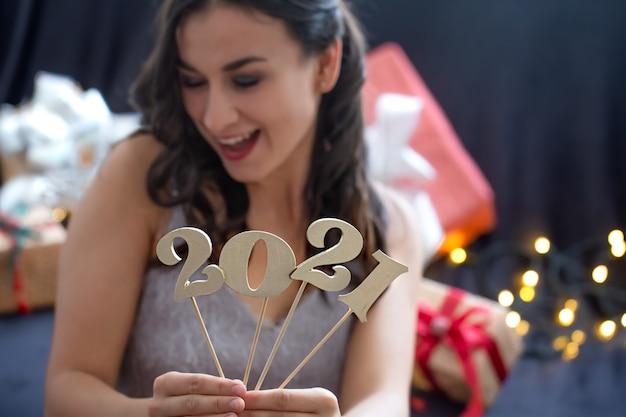 Menina segurando na mão o número do próximo ano em um fundo escuro e desfocado. Foto gratuita