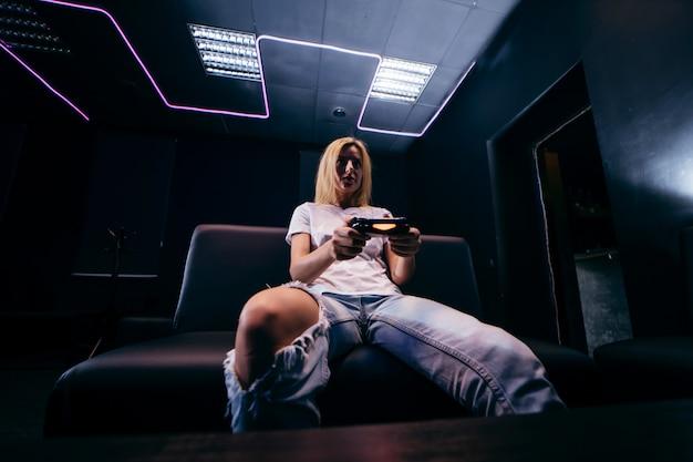 Menina segurando o gamepad nas mãos e jogando videogame Foto Premium