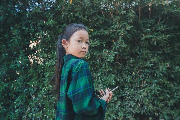 Menina segurando o telefone sozinho. estudo ao ar livre. Foto Premium