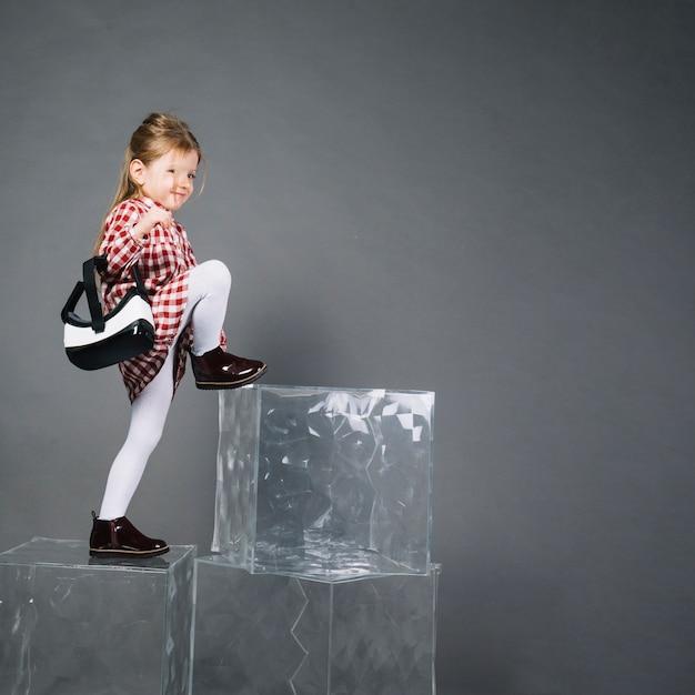 Menina segurando óculos de realidade virtual subindo em blocos transparentes contra fundo cinza Foto gratuita