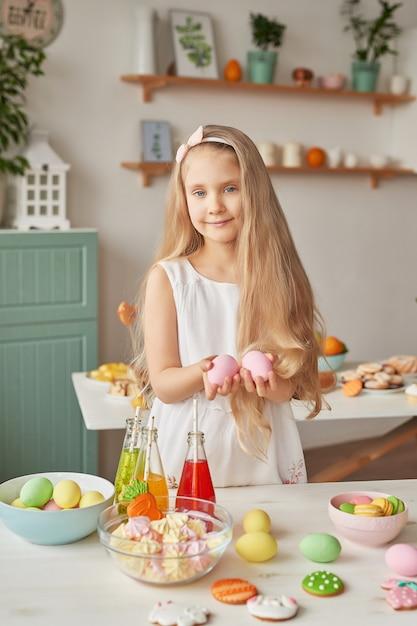 Menina segurando ovos de páscoa na cozinha Foto Premium