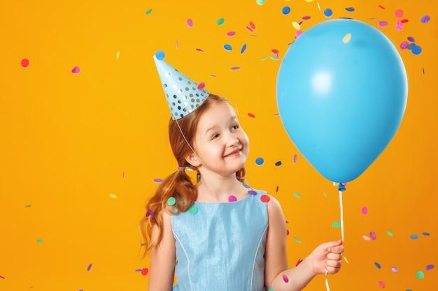 Menina segurando um balão em confetes caindo. Foto Premium