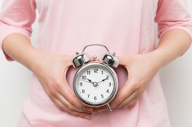 Mulher segurando despertador representando ovulação tardia