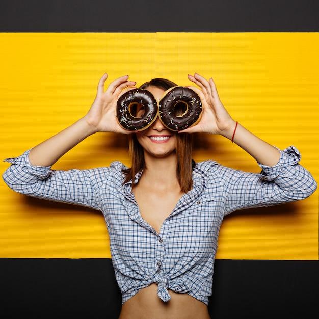Menina segurando um donut com cobertura de chocolate Foto gratuita