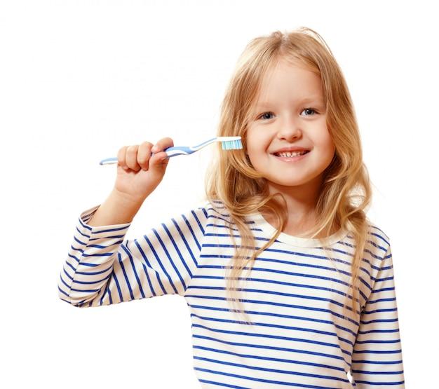 Menina segurando uma escova de dentes. Foto Premium